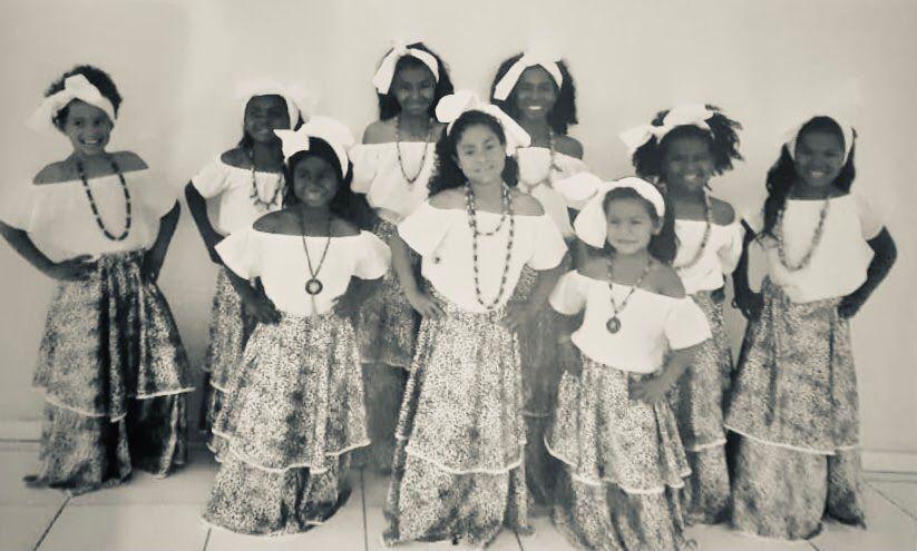 Descrição: Fotografia horizontal, em preto e branco, de nove meninas negras de seis a onze anos. As seis meninas maiores estão atrás, e três menores na linha da frente. Todas elas estão vestidas de baianas, com blusa branca e saia florida até os pés. Todas estão sorrindo, e usam acessórios, como laço de cabelo na cor branca e colares de miçanga.