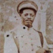 Descrição: Fotografia antiga em retrato, na cor sépia, enquadrada da cintura para cima, de um homem negro vestindo farda policial e um quepe. Com feição séria, o homem olha para a câmera e posiciona suas mãos na altura do estômago. Ao fundo, uma parede de concreto.