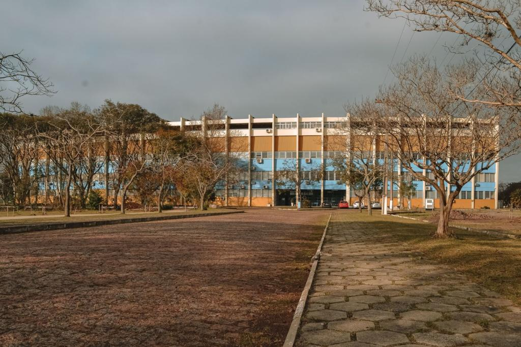 Foto horizontal da vista frontal de um prédio de cinco pavimentos. O prédio está pintado nas cores azul, amarelo e branco. Algumas árvores estão em frente ao prédio e o céu está nublado.