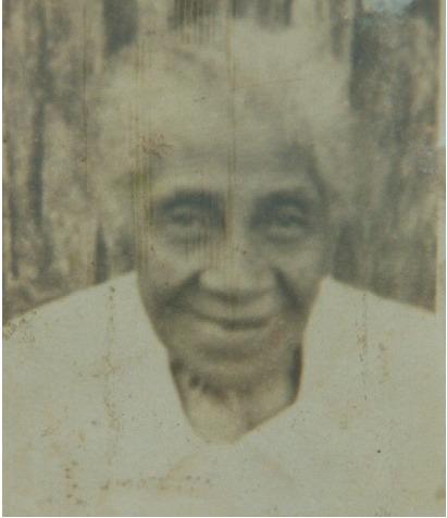 Descrição: Fotografia antiga, enquadrada do peito para cima, na cor sépia, de uma mulher negra idosa, sorrindo timidamente. Ela é magra, com cabelos crespos e brancos, e veste uma camisa branca. Ao fundo, uma parede de madeira escura e rústica.