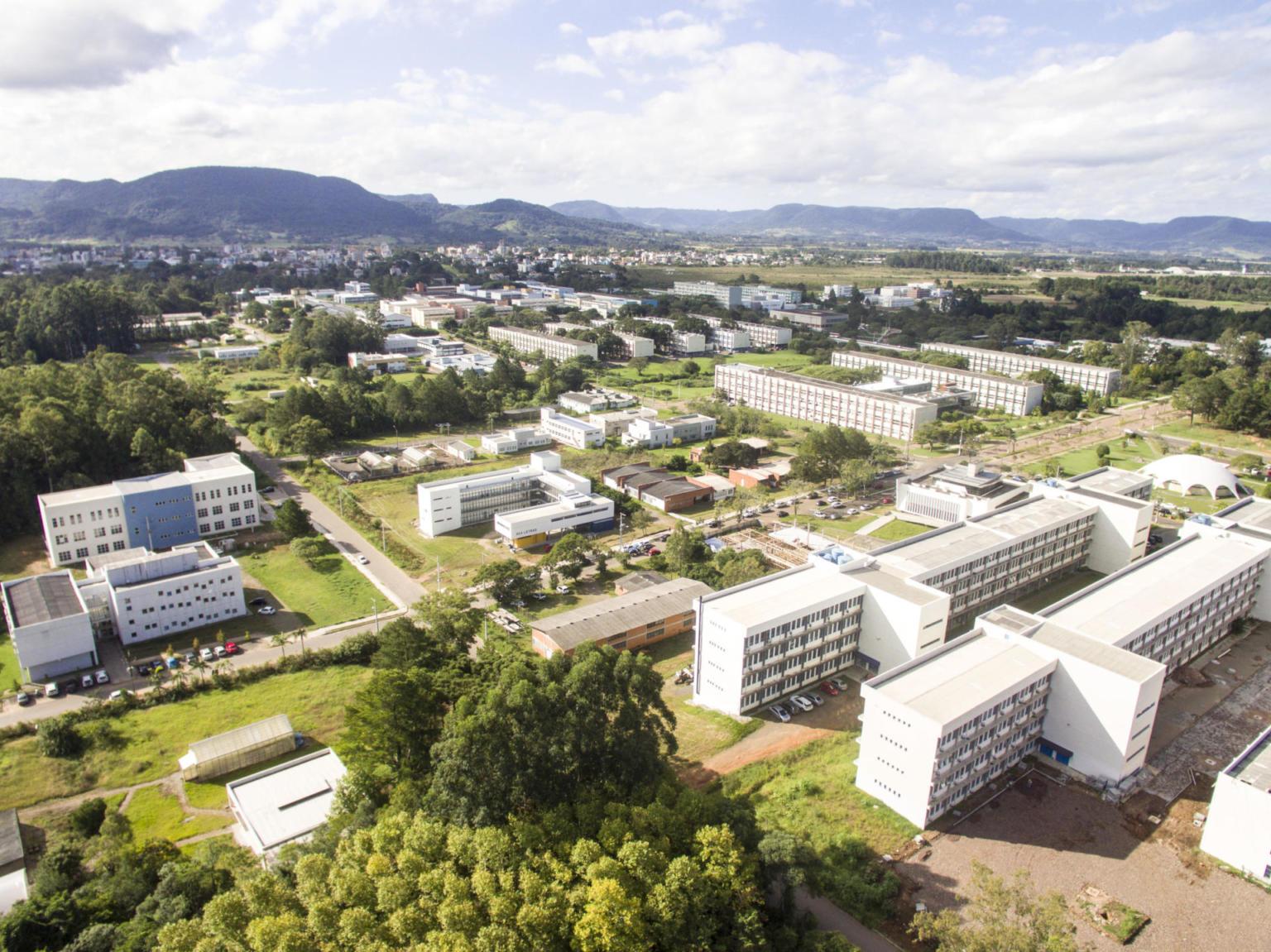 Vista aérea de diversos prédios do campus em meio à área verde