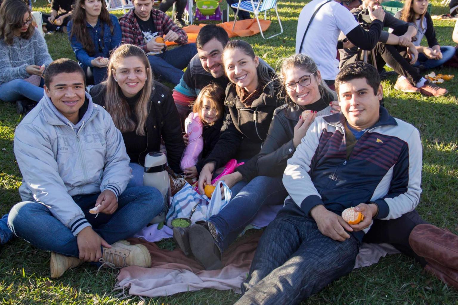 Seis pessoas sentadas no gramado