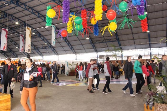 Ginásio cheio de balões coloridos no teto e pessoas circulando