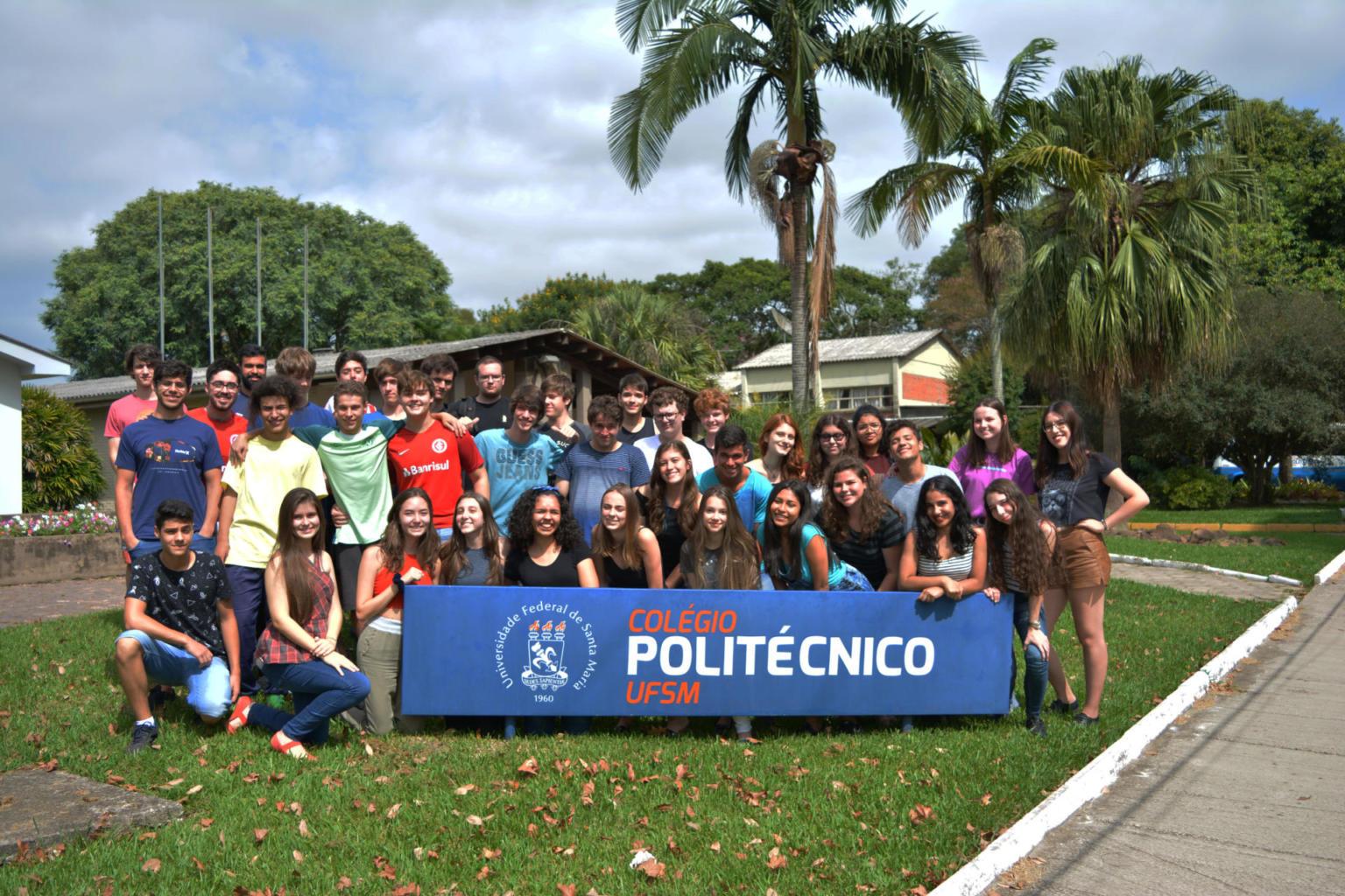 Diversas pessoas atrás de uma placa azul escura do Colégio Politécnico