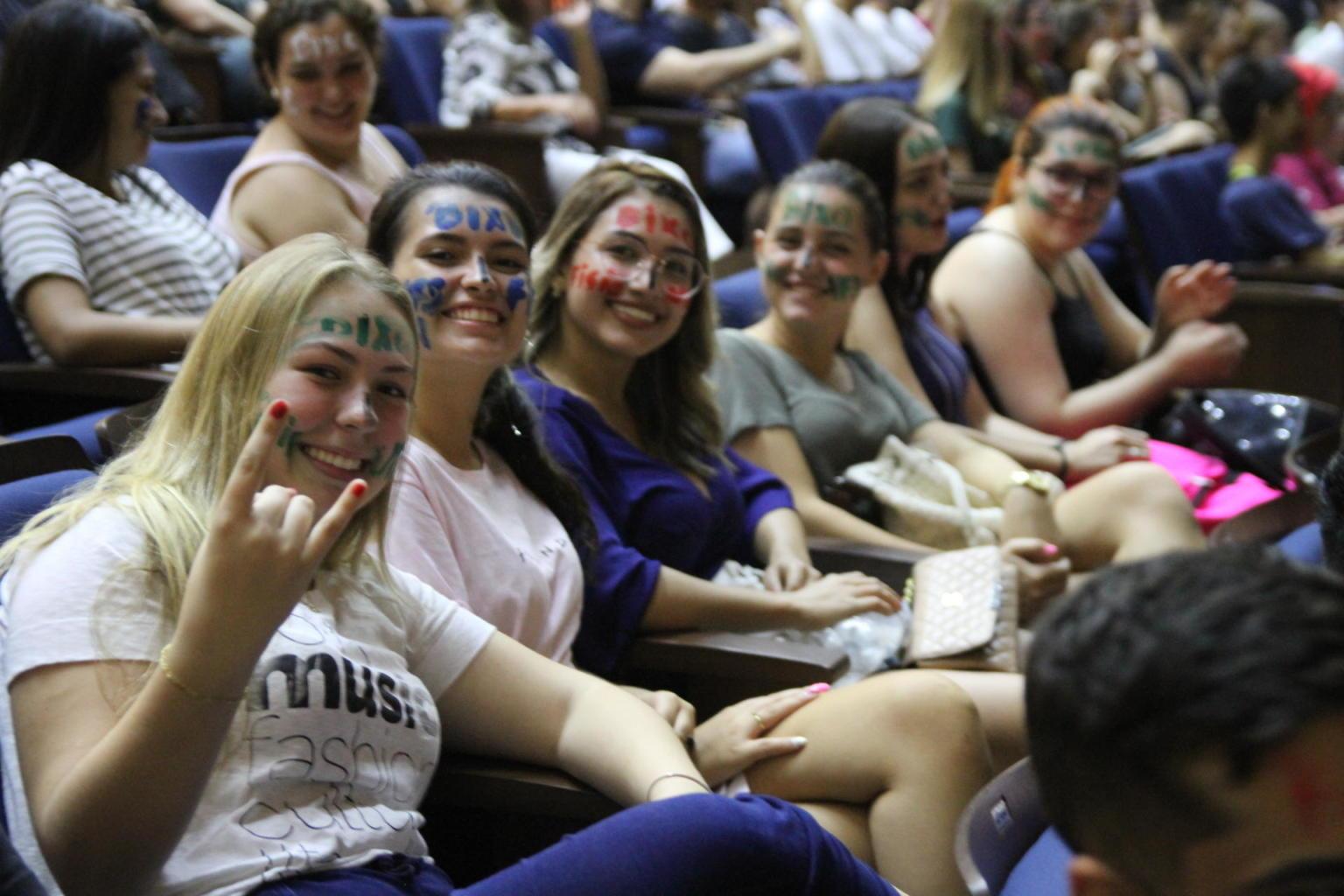 Pessoas sentadas em um auditório com rostos pintados de bixos