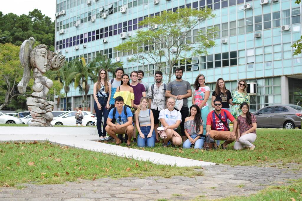Diversas pessoas em pé em frente a prédio azul claro da Reitoria