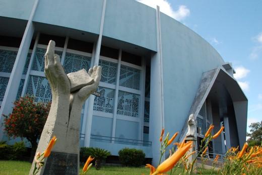 Prédio oval de concreto cinza com mosaicos na janela, em frete flores laranjas e uma estátua de duas mãos abertas em aos céus