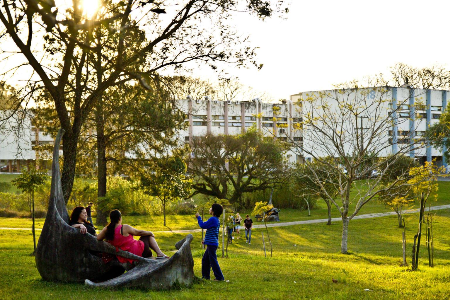 Duas pessoas sentadas e uma brincando em meio ao gramado e às árvores, prédios ao fundo
