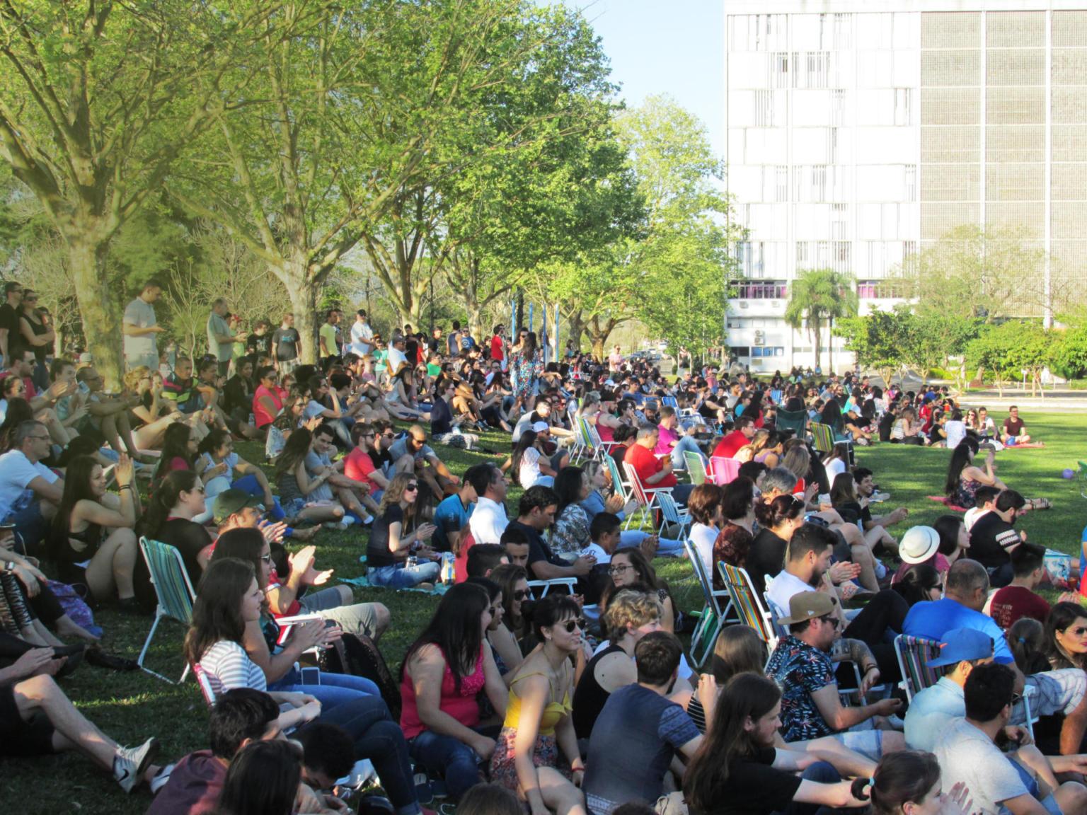 Diversas pessoas sentadas no campus, prédio da Reitoria ao fundo