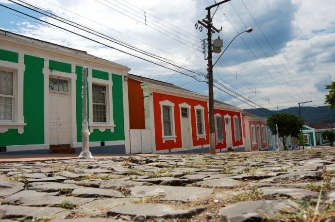 Rua de pedras com casas antigas da Vila Belga, uma verde, uma vermelha e uma rosa com detalhes brancos