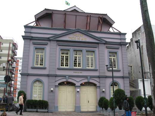 Prédio lilás com portas e janelas brancas