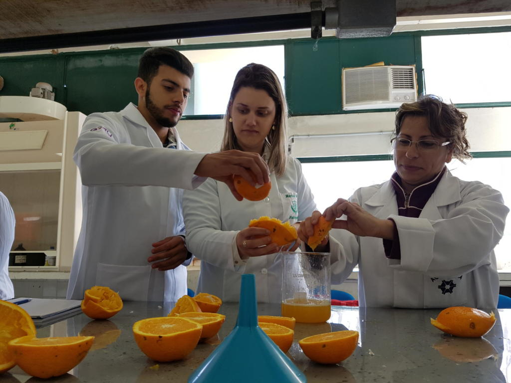 Três pessoas vestindo jaleco branco trabalhando com laranjas em uma bancada