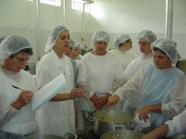 Mulheres de jaleco e touca branca cozinhando
